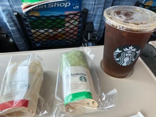 特急スーパーあずさのテーブル上のスターバックスのラップサンドとコーヒー