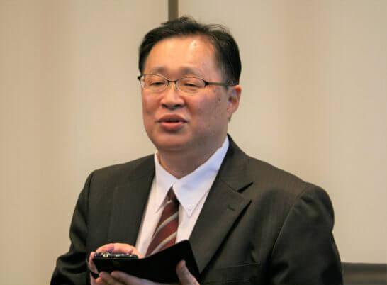 スマホを手に取る岡三オンライン証券 営業推進部長の稲田弘文さん