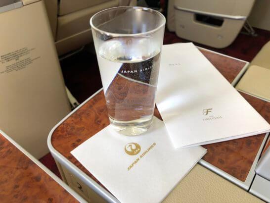 JAL国内線ファーストクラスの森伊蔵(お湯割り)を机においたシーン