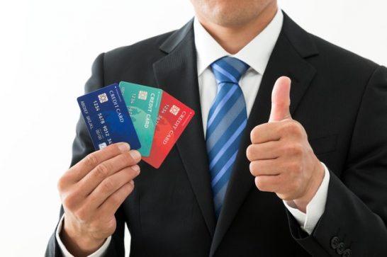 3枚のクレジットカードを手に取る男性
