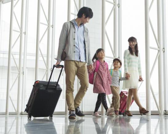 スーツケースを引きずって空港を移動する家族