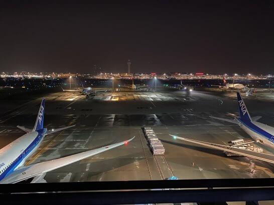 夜の羽田空港国際線ターミナルに駐機するANAの飛行機