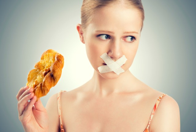 diet concept. woman mouth sealed with duct tape, buns