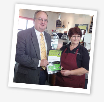 Jean Clark from Brading Roman Villa's Forum Café receives the café's sticker from Cllr Barry Abraham