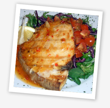 Swordfish steak cooked on a flame barbeque with a Thai lime sweet chilli butter and salad