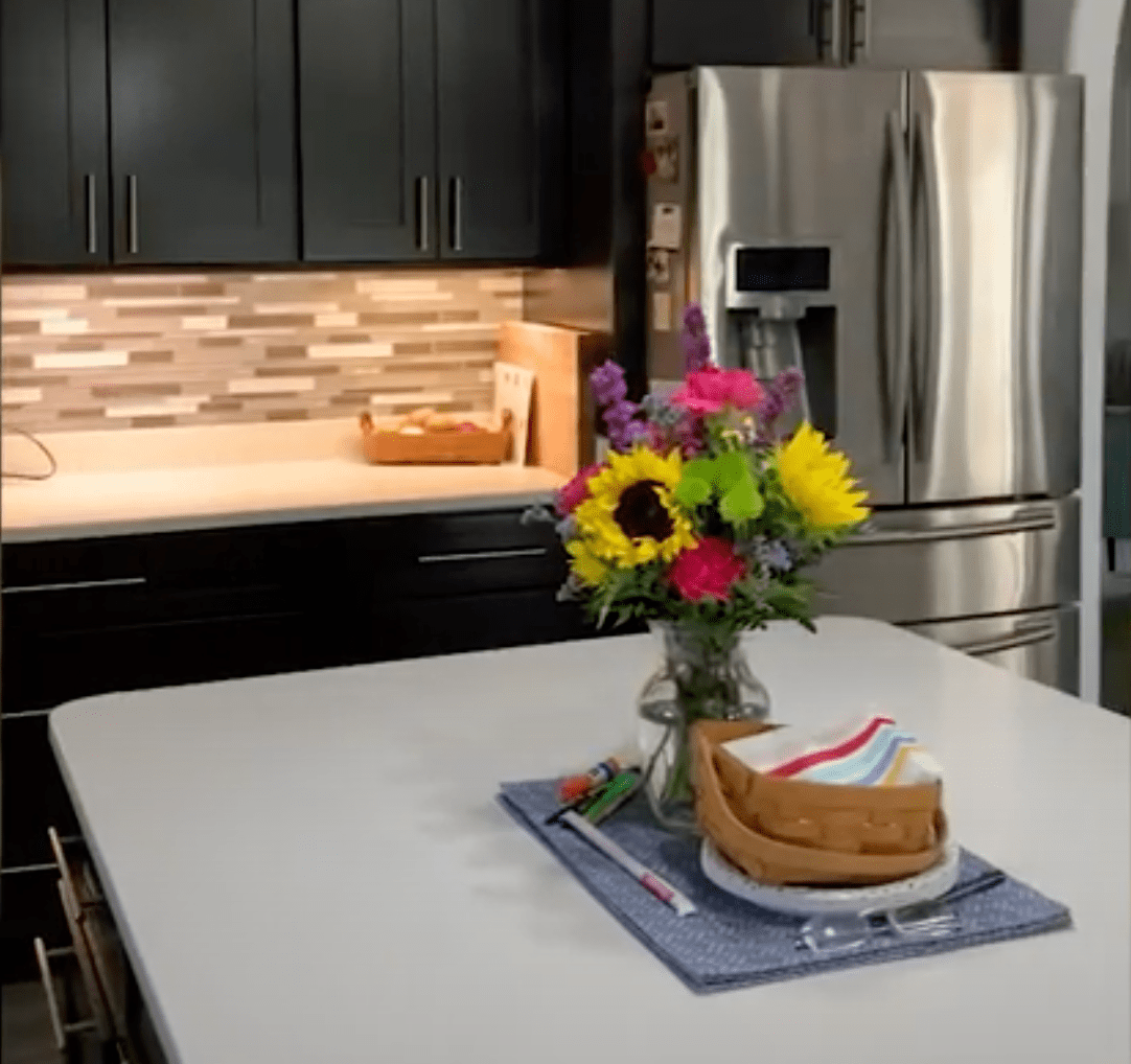 """The """"before"""" photo of a kitchen before cleaning it for real estate photography - a vase of flowers and small baskets on the island and countertops and items are on the refrigerator."""