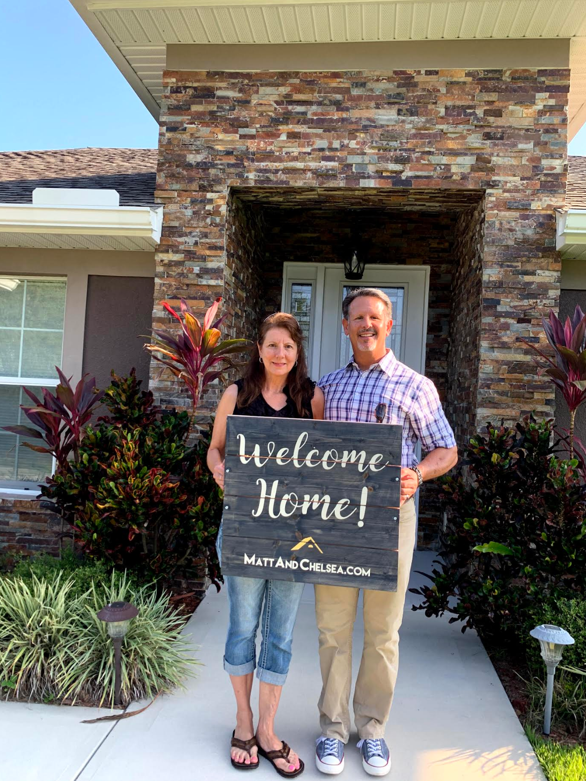"""Photo of clients Brian and Carrie holding a """"Welcome home!"""" sign in front of the home they just bought."""