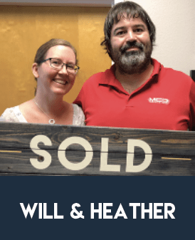"""Photo of clients Will and Heather holding a """"Sold"""" sign after successfully selling their home."""