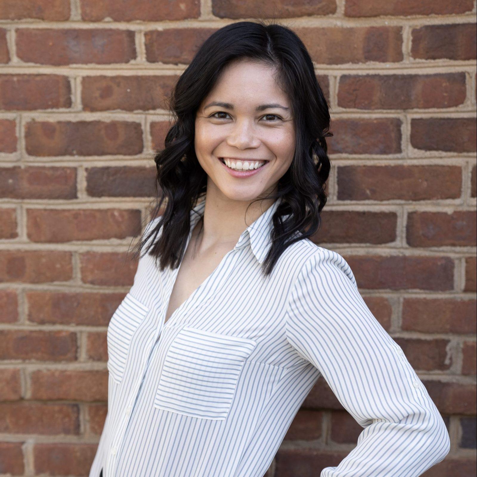 Headshot of Cheyenne Kiddy on a brick background.