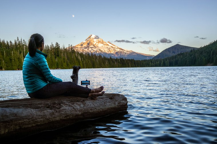 Woman sitting on a log taking a time lapse video of sunset on Mt. Hood, Oregon.