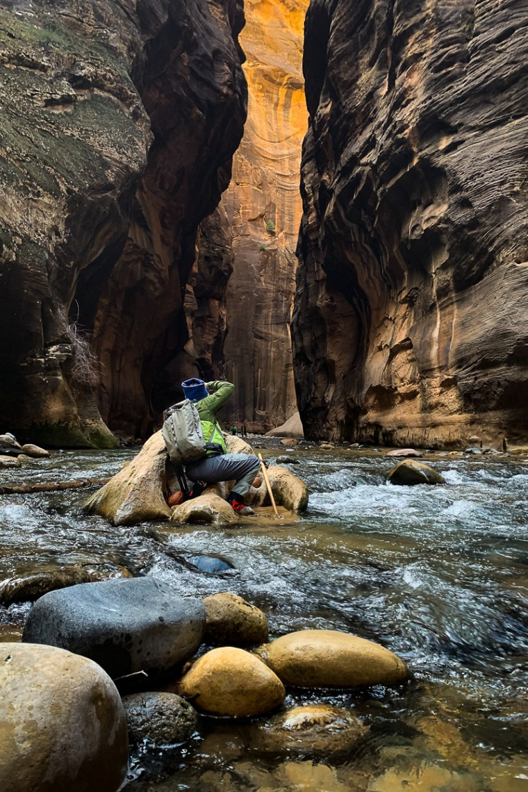 Photographer kneeling behind boulder in a stream photographing a section of Zion Narrows in Zion National Park.