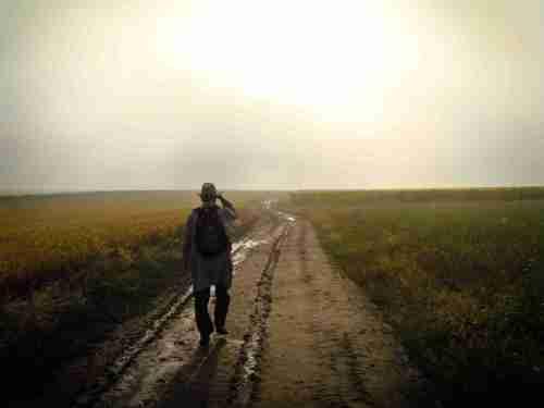 Man Walking on Dirt Road