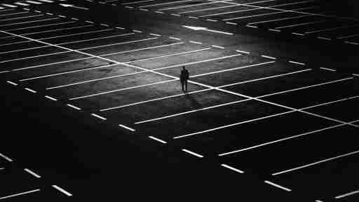 Picture of a man alone in a huge, dark parking lot.