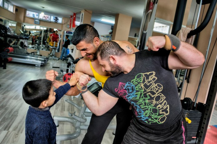 39-year-old Syrian bodybuilder, Ibrahim Shehabi, challenging another bodybuilder at the gym, and his 6-year-old son Radwan judges his father to be the strongest man. Istanbul, Turkey 2016. © Matteo Bastianelli