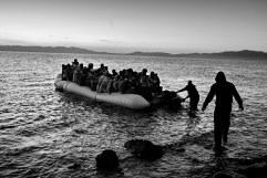 Four men approaches a rubber dinghy full of Syrians refugees in order to take away its outboard motor and fuel tanks. About 600 asylum seekers reach the island shore everyday, each one of them paying 1 thousand dollars in order to cross the Aegean Sea and reach the Greek coast. Kratigos, Lesbos, Greece 2015. © Matteo Bastianelli