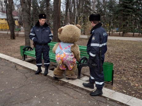 Two policemen are watching a man dressed as a bear in the city center. Chisinau, Moldova 2014. © Matteo Bastianelli