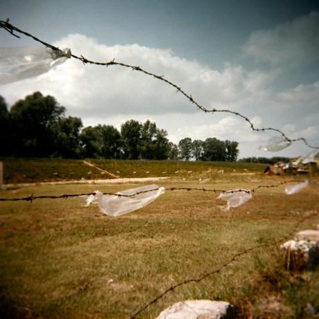 A fence separates an area designated for a Rom commune from adjacent fields. Podturen (Međimurje), Croatia 2009. © Matteo Bastianelli