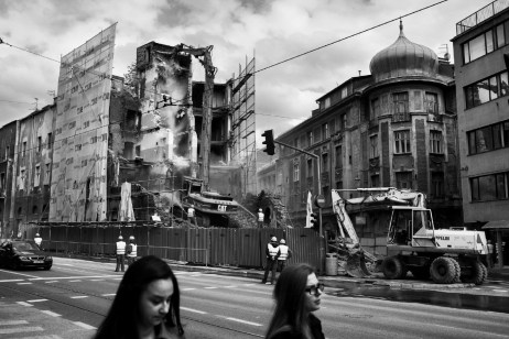 Two girls walking while men at work are involved in the demolition of the former Hotel Zagreb, a national monument of BiH. During the war, Hotel Zagreb was hit by grenades, burned and fully destroyed. The building will soon be returned to its original state. Sarajevo, Bosnia and Herzegovina, 2014. © Matteo Bastianelli