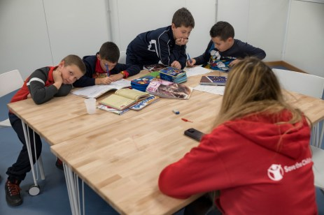 "Some kids are seen doing their homework followed by a teacher from Save the Children, at the 2.0 Youth Center. Amatrice, Italy 2016. © Matteo Bastianelli for ""La Stampa"""