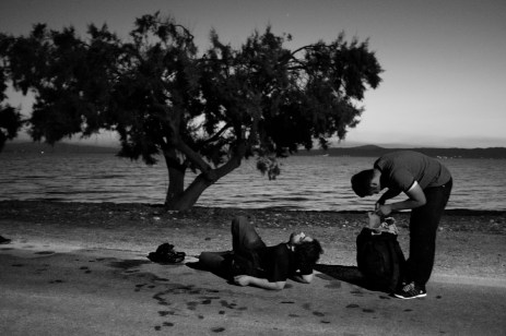 Some Syrian refugees just arrived from the coastal town of Dikili, Turkey, take a rest on the street. Kratigos, Lesbos, Greece 2015. © Matteo Bastianelli