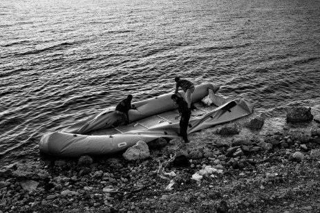 Three men destroy a rubber dinghy by cutting it with knives. The vessel arrived around one hour beforehand carrying about 50 asylum seekers from the Turkish coast to the Greek island. Kratigos, Lesbos, Greece 2015. © Matteo Bastianelli