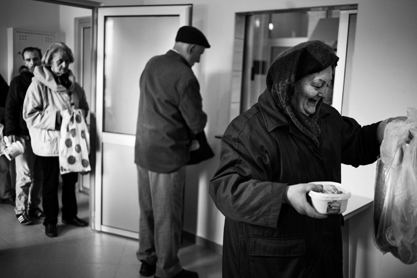 """Some people in line to receive food at the headquarters of the Catholic organization """"Saint Antonio"""", in the Dobrinja district. According to the World Bank, 1 in 5 Bosnian lives below the poverty line. Sarajevo, Bosnia and Herzegovina 2014. © Matteo Bastianelli"""