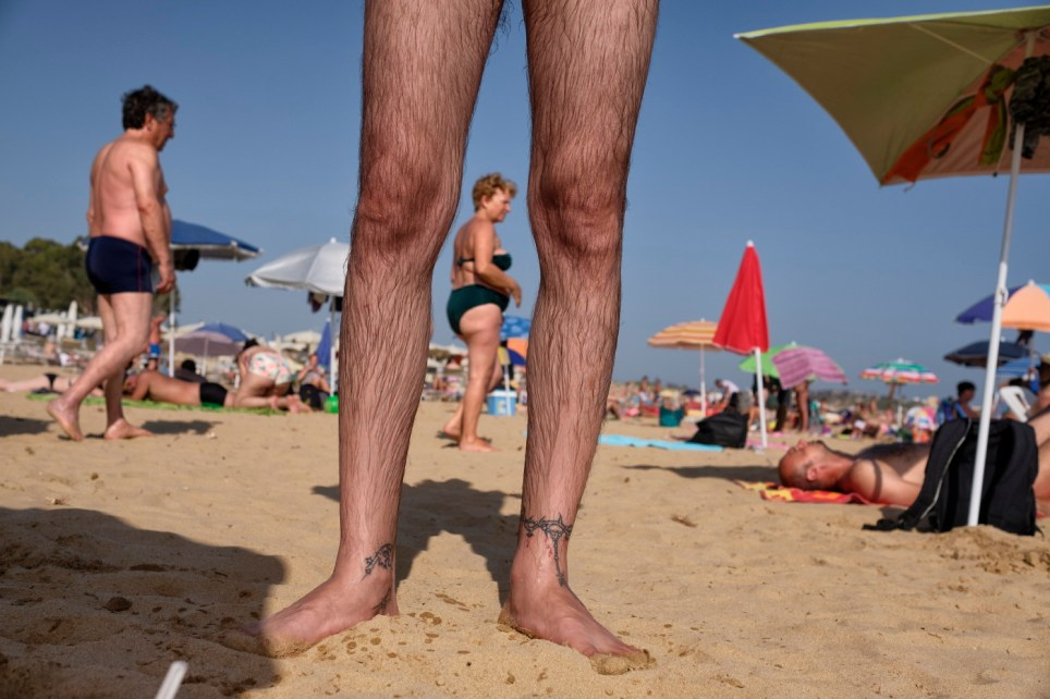 34-year-old Alessandro Raudino, who has been suffering from multiple sclerosis since 2006, is seen on the beach with tourists and swimmers in the background. Marina di Modica (Ragusa), Italy 2016. © Matteo Bastianelli
