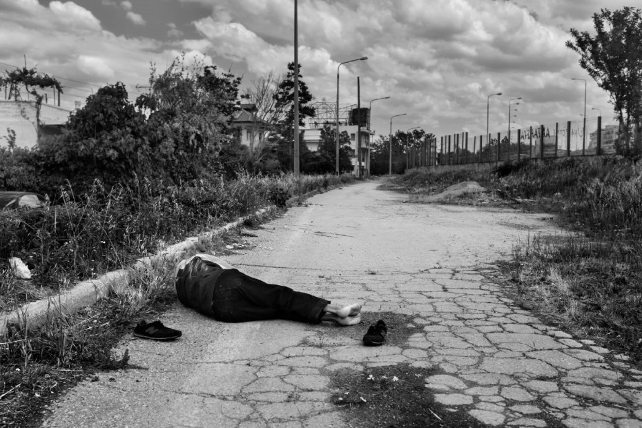 """An Afghan man sleeping at the side of the road near the """"Macedonia"""" bus station. Thessaloniki, Greece 2015. © Matteo Bastianelli"""