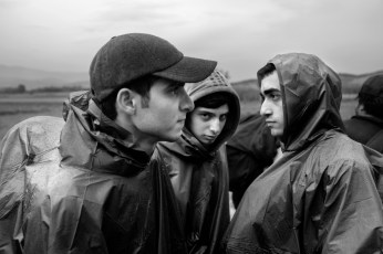 Three Syrian youths taking a break on their way to the border between Greece and FYROM. Evzoni, Greece 2015. © Matteo Bastianelli