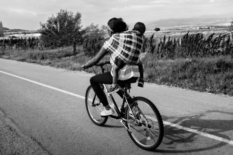 An Eritrean asylum seeker with her son on a bicycle on their way to the border between Greece and the Republic of North Macedonia. Evzoni, Greece 2015. © Matteo Bastianelli