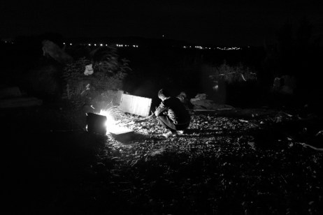 A refugee lights a fire to warm himself during a cold night in the buffer zone between the Republic of North Macedonia and Greece. Idomeni, Greece 2015. © Matteo Bastianelli