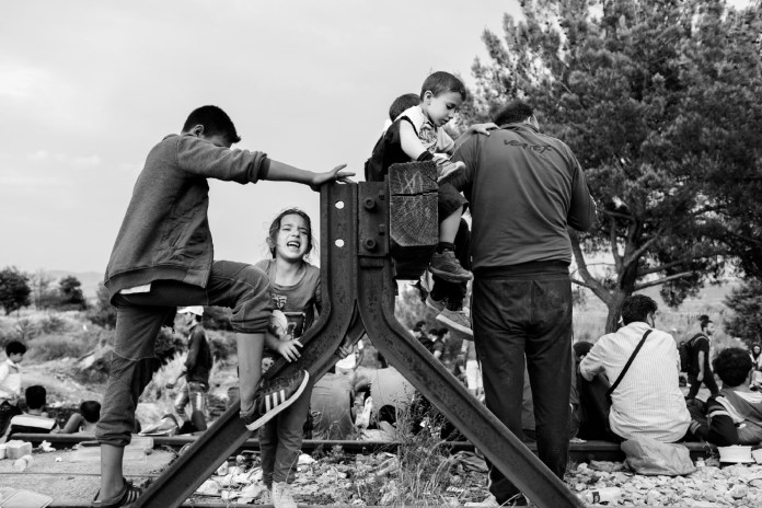 A little girl screams while other asylum seekers are seen waiting for the FYROM border police to give permission to enter the country. Idomeni, Greece 2015. © Matteo Bastianelli