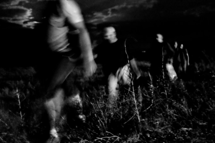 A group of Syrian asylum seekers walking through cultivated fields in order to reach the border between Greece and the Republic of North Macedonia, after border police had driven them back to Greece. Evzoni, Greece 2015. © Matteo Bastianelli