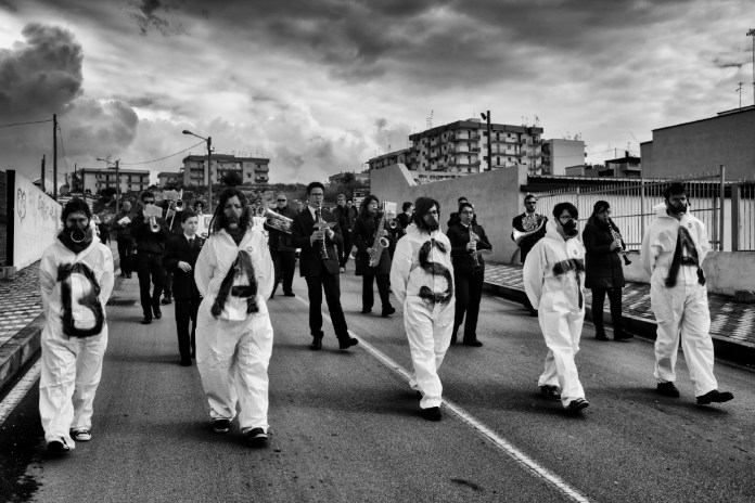 "A crowd of people wearing hazmat suits that say ""STOP"", are seen protesting against the environmental pollution afflicting the town. Statte (Taranto), Italy 2014. © Matteo Bastianelli"