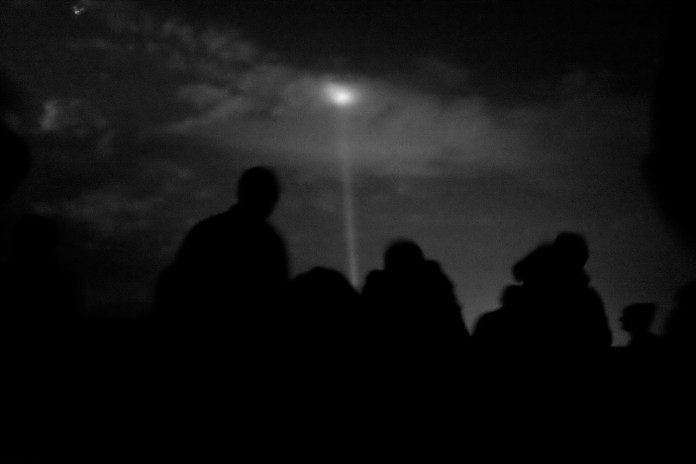 A group of Syrian asylum seekers watch the lights of one of the casinos in Gevgelija, Republic of Macedonia (FYROM) 2015. © Matteo Bastianelli