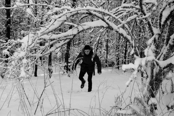 """23-year-old Syrian refugee Mohamad Al Masalmeh walks along a path in the Arnsberg Forest Nature Park. """"It's beautiful here, but it reminds me too much of the forest between Romania and Hungary, a real nightmare"""", Mohamad claims. In fact, a year earlier, he had to pay a smuggler and walk through the snow for hours before he could catch a train to reach Germany. Warstein, Germany 2016. © Matteo Bastianelli"""