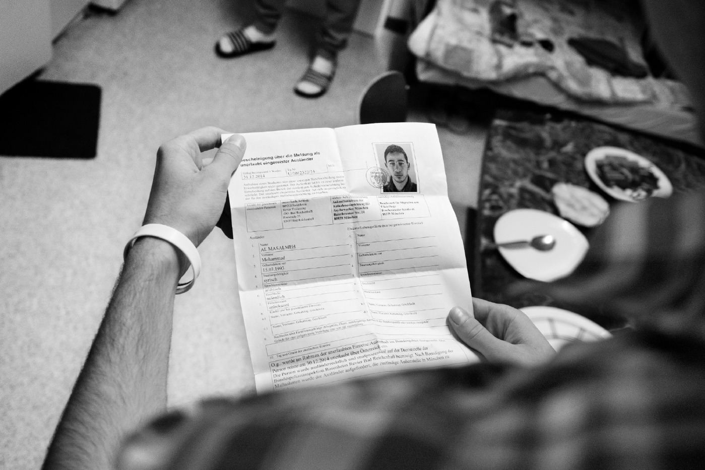 21-year-old Syrian asylum seeker Mohamad Al Masalmeh looks at the document he received from the German police, who took his Bulgarian passport. Warstein, Germany 2014. © Matteo Bastianelli