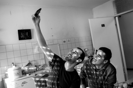 Syrian asylum seekers Mohamad and Hani Al Masalmeh take a self-portrait of themselves in the room where they are living inside a facility for refugees. Warstein, Germany 2014. © Matteo Bastianelli