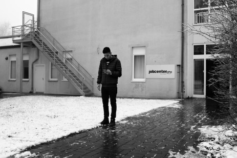 23-year-old Syrian refugee Mohamad Al Masalmeh waits for his cousin Hani outside the job centre in the town. Belecke (Warstein), Germany 2016. © Matteo Bastianelli