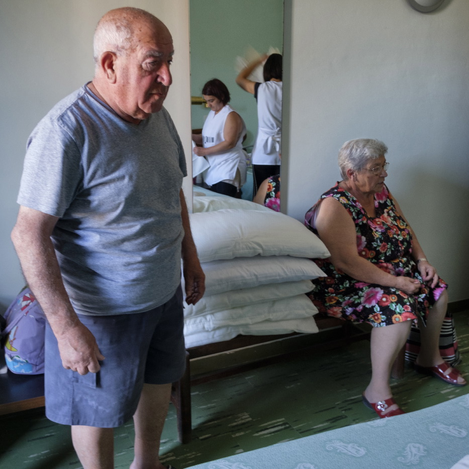 80-year-old Sabatino is seen with his 71-year-old wife Annamaria waiting for the cleaning ladies of the hotel to finish tidying their room. Grottammare, Italy 2017. © Matteo Bastianelli