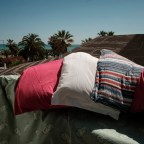 Pillows and sheets hanging in the sun on the balcony of the hotel room where 43-year-old Marika is temporarily staying with her family. Grottammare, Italy 2017. © Matteo Bastianelli