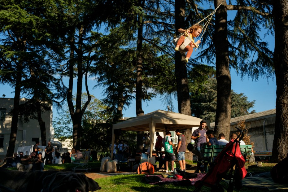 """Some visitors at the industrial hemp and medical cannabis fair """"Canapa in Mostra"""", are seen relaxing in the garden at the complex while a child plays on a swing hanging from a tree branch. Naples, Italy 2016. © Matteo Bastianelli"""