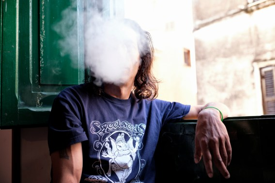 "Fabio Tamburlani, founder of the ""Cannabis Cura Cori"" association, is hidden behind a cloud of smoke. Cori (Latina), Italy 2016. © Matteo Bastianelli"