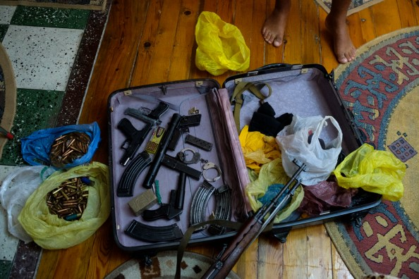 A drug trafficker is seen in front of a suitcase with weapons, plastic bags with full metal jacket bullets, ammunition, a Chinese-made carbine model 56, handcuffs and a detonator operable by phone, that he holds illegally inside a house in Albania 2017. © Matteo Bastianelli