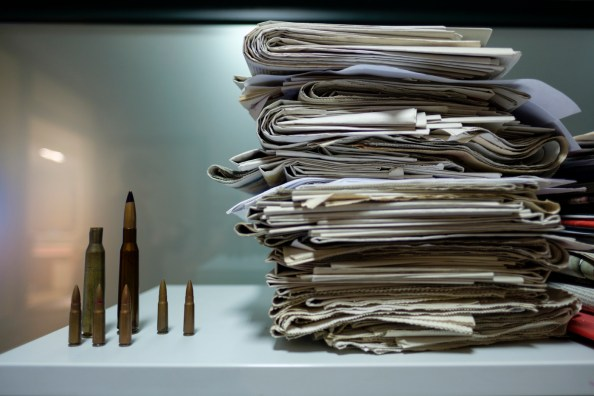 "Some newspapers next to the bullets that Artan Hoxha, a 43-year-old Albanian investigative journalist for the ""24 News"" TV, keeps in his office, including the one used by drug cartels to threaten him, some of those fired by drug traffickers against police helicopters during the siege of Lazarat in 2014 and some of the Civil War of 1997. Tirana, Albania 2017. © Matteo Bastianelli"