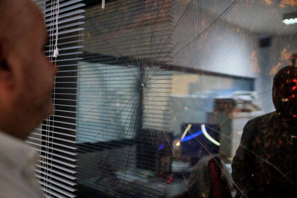 """Artan Hoxha, a 43-year-old Albanian investigative journalist for the """"24 News"""" TV, is seen inside his office, in front of a window, whose glass was broken to intimidate him. Artan has received several death threats and he was kidnapped by drug cartels for the work he is carrying out. Tirana, Albania 2017. © Matteo Bastianelli"""