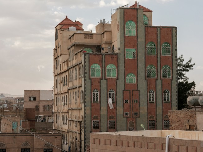 A thobe or dishdasha, a white tunic commonly worn by all men in the Arabian Peninsula, hangs out to dry from a window. The distinctive architecture of the buildings in Sana'a is visible in the diplomatic area of the capital. Sana'a, Yemen 2018. © Matteo Bastianelli