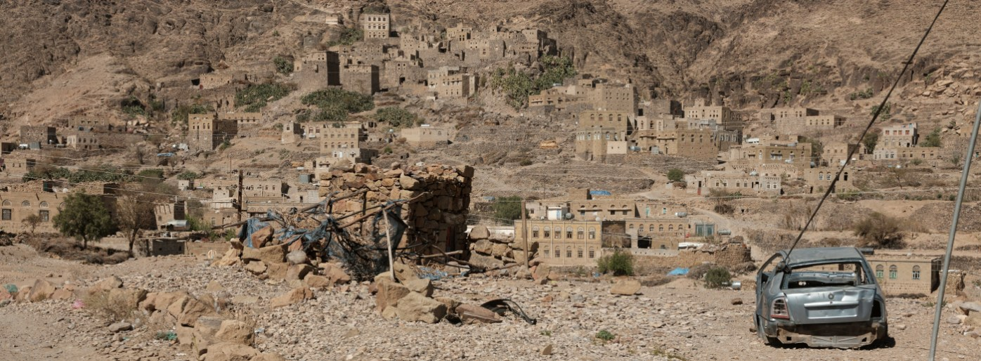 A wrecked car in the vicinity of a village left unharmed by the conflict and located between Sana'a and Damar, Yemen 2018. © Matteo Bastianelli
