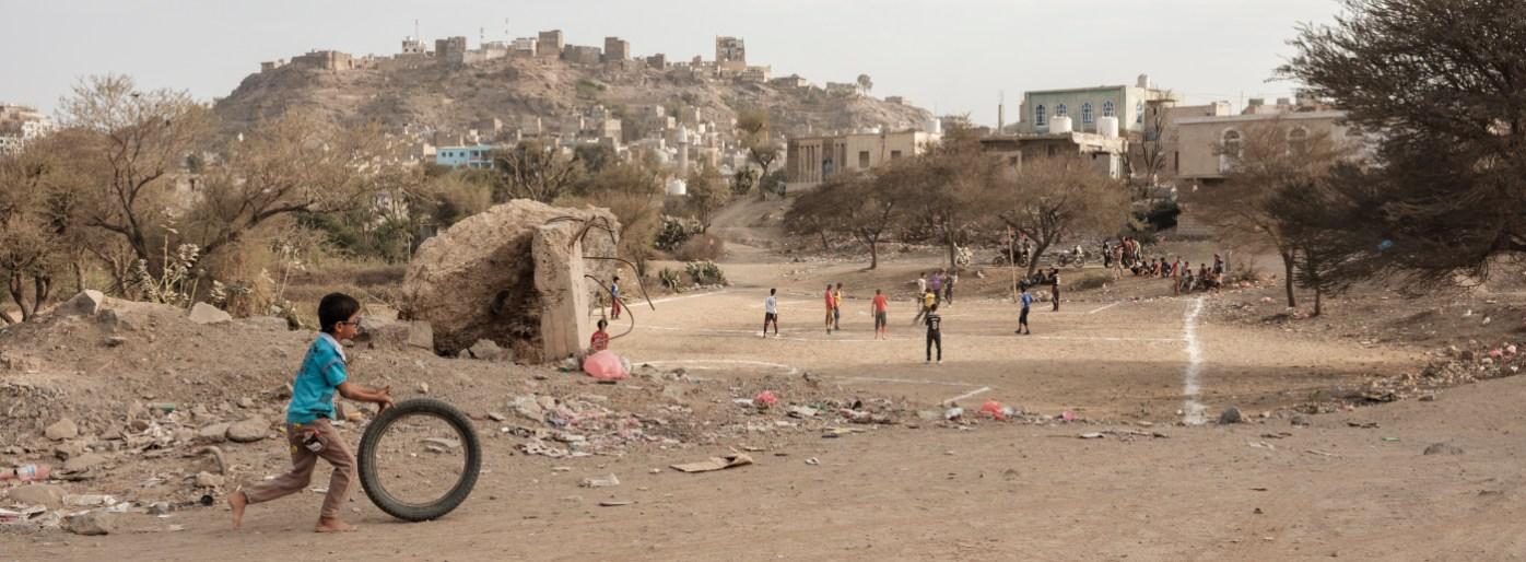 A child pushes a tyre in the vicinity of a makeshift football field where some boys are seen playing. In the background are the remains of the Medina (old town), heavily damaged by the war. Ad Dhale, Yemen 2018. © Matteo Bastianelli
