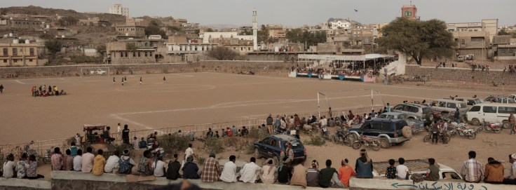 Men gathered at the local stadium, are seen watching a football match. Life goes on despite the war that has been ravaging the country for 4 years. Ad Dhale, Yemen 2018. © Matteo Bastianelli